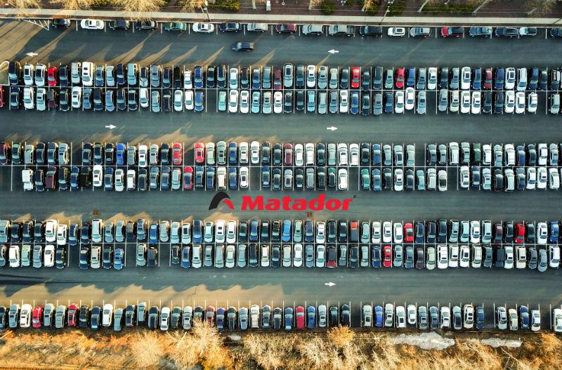 Parkering med massa bilar. Matador - logotyp ses i mitten.